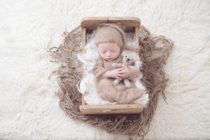 Newborn fotografie, kleine baby slapend in bedje met zijn bruine pakje, mutsje en lieve teddy beer
